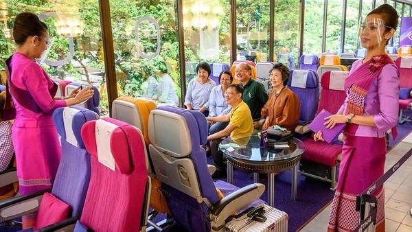 Salah satu maskapai penerbangan di Thailand memberikan pengalaman sensasi makan di dalam pesawat untuk pengunjung. (AFP)