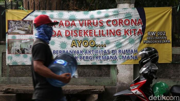 Warga melintasi spanduk bahaya COVID-19 di Komplek DKI, Pondok Kelapa, Jakarta Timur, Selasa (15/9/2020). Berbagai cara terus dilakukan untuk mensosialisasikan bahaya COVID-19 hingga lingkungan perumahan RT dan RW.