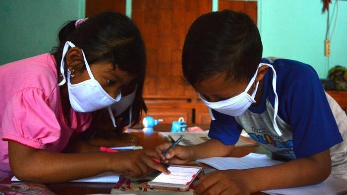 Sejumlah siswa kelas 6 SDN Sumberaji 2 mengerjakan tugas pelajaran sekolah secara daring atau online di kawasan makam Dusun Ngapus, Desa Sumberaji, Kecamatan Kabuh, Kabupaten Jombang, Jawa Timur.