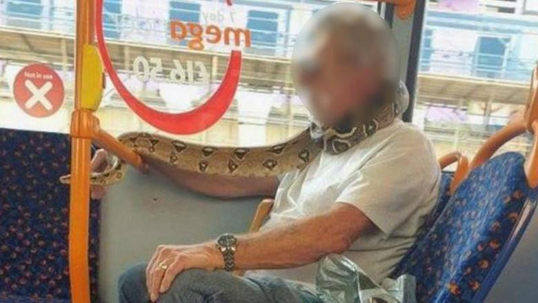 Seorang pria terlihat mengenakan Masker Ular di Manchester, inggris.
