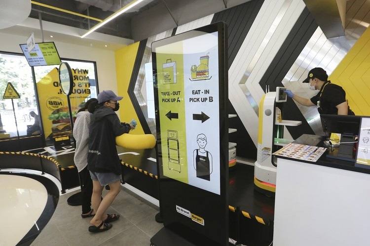 In this Sunday, Sept. 13, 2020, photo, a robot carries a takeout bag with food at No Brand Burger in Seoul, South Korea. From order to pick-up, customers don't need a single face-to-face interaction. All they need to do is to click the menu they want on a kiosk touchscreen, pay and wait for a serving robot to bring their takeout bag to the pick-up spot. (AP Photo/Ahn Young-joon)