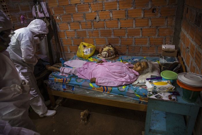 Government team members prepare to remove the body of Cruz Amanda Vargas, who died from symptoms related to the new coronavirus at the age of 84, from inside her home, in the Shipibo Indigenous community of Pucallpa, in Peru's Ucayali region, Monday, Aug. 31, 2020.  At the peak of the outbreak in May and June, around 15 people were dying a day, said Juan Carlos Salas, director of Ucayali's regional health agency. (AP Photo/Rodrigo Abd)