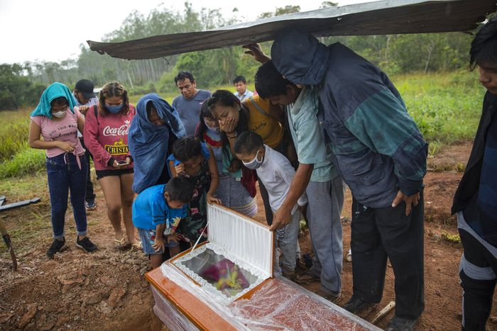 Children watch a government team remove the body of Susana Cifuentes, who died from symptoms related to the new coronavirus at the age of 71, in the Shipibo Indigenous community of Pucallpa, in Peru's Ucayali region, Monday, Aug. 31, 2020. The Shipibo had tried to prevent COVID-19's entrance by blocking off roads and isolating themselves. But in May many came down with fevers, coughs, difficulty breathing and headaches. (AP Photo/Rodrigo Abd)
