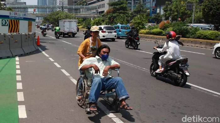 Trotoar di Jalan Thamrin, Jakarta Pusat, digunakan dalam proyek MRT. Hal ini membuat seorang pengguna kursi roda terpaksa melintas di tengah jalan.