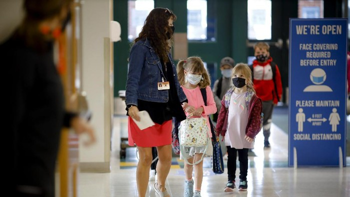 Kindergarten students are led into the building on the first day of in-person classes at Lee Elementary School on Wednesday, Sept. 16, 2020  in Lee, Mass. (Stephanie Zollshan/The Berkshire Eagle via AP)
