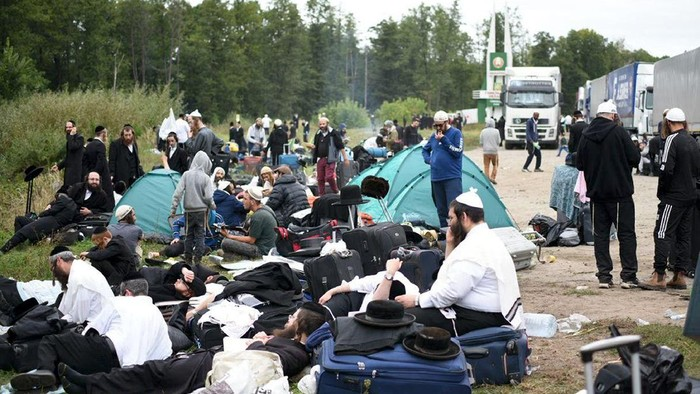 Jewish pilgrims sit on the Belarus-Ukraine border, in Belarus, Tuesday, Sept. 15, 2020. About 700 Jewish pilgrims are stuck on Belarus border due to coroavirus restrictions that bar them from entering Ukraine. Thousands of pilgrims visit the city each September for Rosh Hashana, the Jewish new year. However, Ukraine closed its borders in late August amid a surge in COVID-19 infections. (TUT.by via AP)
