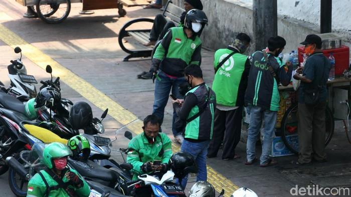 Ojek online dan taksi diijinkan beroperasi selama PSBB DKI Jakarta. Namun di kawasan Senayan, mereka terlihat berkerumun saat menunggu penumpang.