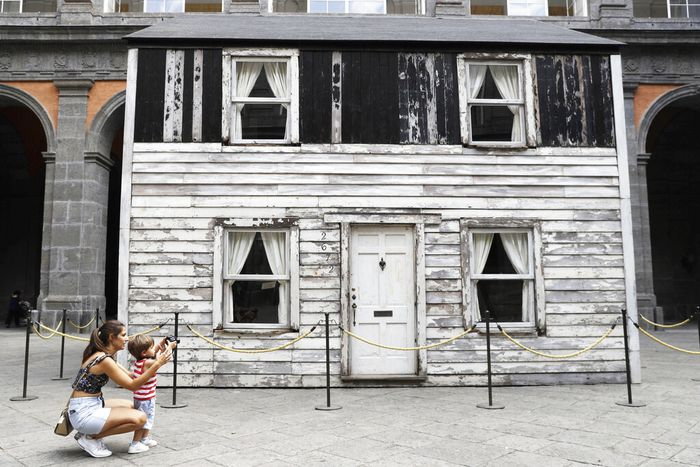 Visitors look through a window of the house of U.S. civil rights campaigner Rosa Parks, rebuilt by artist Ryan Mendoza, for public display, in Naples, Italy, Tuesday, Sept. 15, 2020. It's the latest stop for the house in a years-long saga that began when Parks' niece saved the tiny two-story home from demolition in Detroit after the 2008 financial crisis. (AP Photo/Gregorio Borgia)