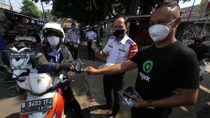 Gojek menggelar aksi Jaga Kesehatan, Kebersihan & Keamanan (J3K) di Depok,Jawa Barat, Kamis (17/9). Mereka juga membagikan masker kapada warga.