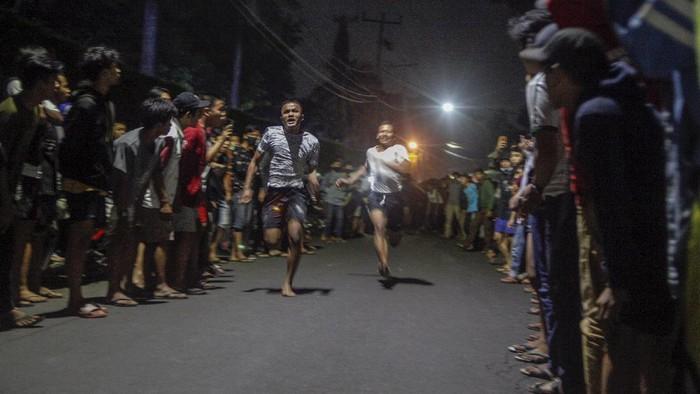 Dua orang pebalap lari liar adu lari berjarak 100 meter di Jalan Raya Ciri Mekar, Cibinong, Kabupaten Bogor , Jawa Barat, Sabtu dini hari (12/9/2020). Menurut mereka balap lari liar ini lebih positif ketimbang balap motor dan balap mobil liar yang selama ini ada di kota-kota besar di Indonesia, walaupun kegiatan itu mengganggu lalu lintas di kawasan tersebut. ANTARA FOTO/Yulius Satria Wijaya/hp.