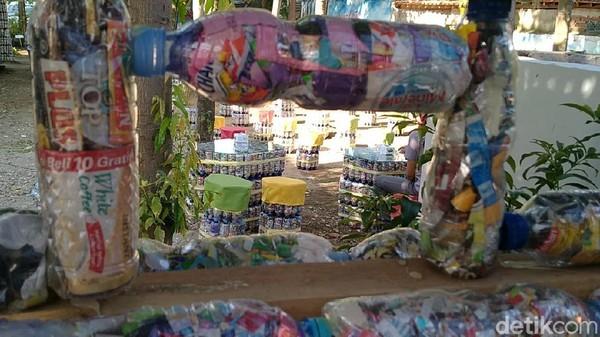 Tumpukan bekas botol air mineral yang berisi plastik bungkus permen atau kopi instan ini nampak rapi tersusun. Ribuan ekobrik ini dibuat untuk kursi, meja, pagar taman, gapura taman bahkan, hingga sebuah bangunan rumah green house.