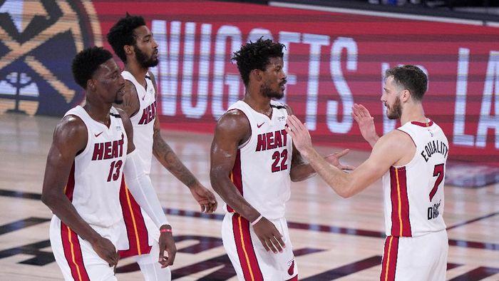 Miami Heats Bam Adebayo (13), Derrick Jones Jr., left rear, Jimmy Butler (22) and Goran Dragic (7) celebate after their NBA conference final playoff basketball game against the Boston Celtics on Thursday, Sept. 17, 2020, in Lake Buena Vista, Fla. (AP Photo/Mark J. Terrill)