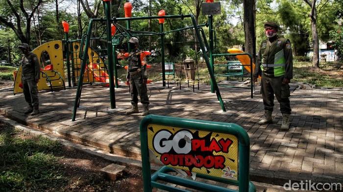 Petugas Satpol PP berjaga di kawasan Taman Jogging Kelapa Gading, Jakarta Utara, yang ditutup, selama PSBB ketat. Taman tersebut terpaksa ditutup karena masuk dalam daftar penutupan tempat saat masa PSBB ketat.