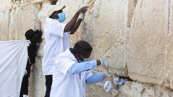 Para pekerja membersihkan catatan doa yang ditinggalkan pengunjung dari sela-sela batu Tembok Barat di Yerusalem.