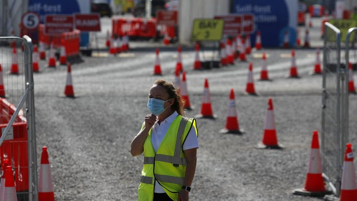 Staff waits in front of empty lanes of a Covid-19 drive thru testing facility at Twickenham stadium in London, Thursday, Sept. 17, 2020. Britain has imposed tougher restrictions on people and businesses in parts of northeastern England on Thursday as the nation attempts to stem the spread of COVID-19, although some testing facilities remain under-utilised. (AP Photo/Frank Augstein)