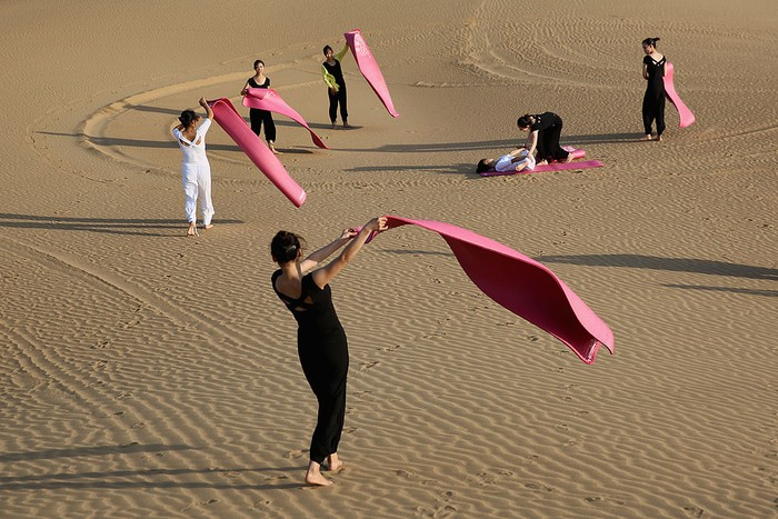 ORDOS, CHINA - JULY 20:  Dancers perform yoga on the dunes of Xiangshawan Desert, also called Sounding Sand Desert on July 20, in Ordos of Inner Mongolia Autonomous Region, China. Xiangshawan is China's famous tourist resort in the desert. It is located along the middle section of Kubuqi Desert on the south tip of Dalate League under Ordos City. Sliding down from the 110-metre-high, 45-degree sand hill, running a course of 200 metres, the sands produce the sound of automobile engines, a natural phenomenon that nobody can explain.  (Photo by Feng Li/Getty Images)