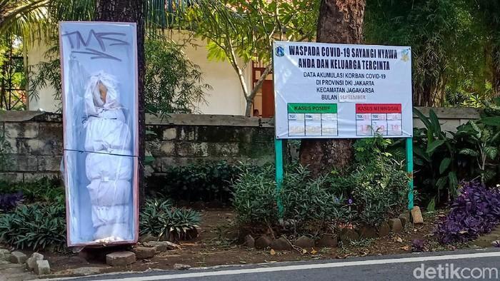 Instalasi peti mati untuk mengkampanyekan bahaya COVID-19 juga dipasang di Jagakarsa, Jakarta Selatan. Dalam instalasi itu, replika peti mati disandarkan di batang pohon.