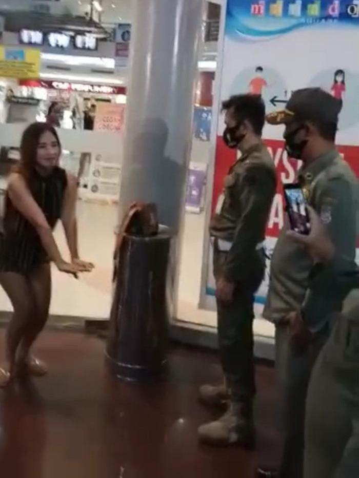 Viral petugas berkeliling menonton wanita tak bermasker yang dihukum di sebuah mal di Manado (Screenshot video viral)