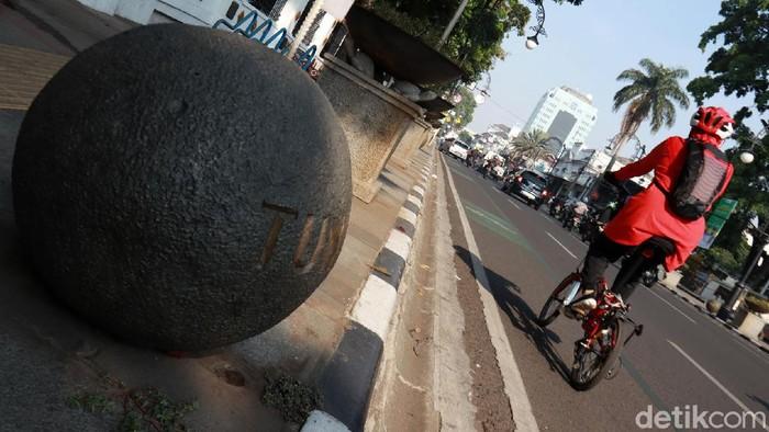 Bendera yang ada di batu granit berbentuk bulat dan bertuliskan negara-negara di Jalan Asia Afrika bercopotan. Bendera yang berbahan baku stiker itu copot dari besinya.
