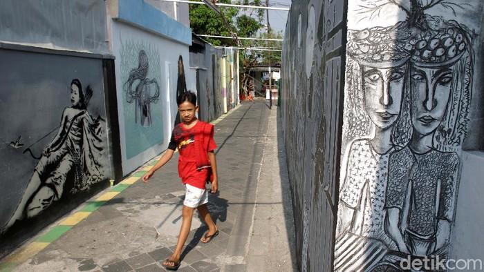 Belasan seniman mural kerja bersama-sama mengecat mural di tembok rumah warga di Kampung Taman, Tamansari, Yogyakarta. Yuk lihat.