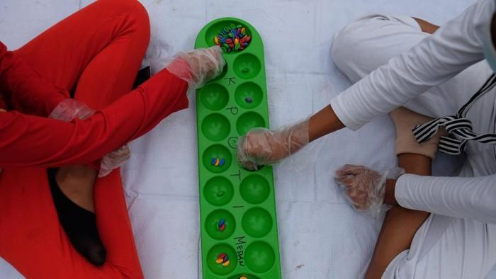 Dua bocah bermain congklak dengan menerapkan protokol kesehatan di Lapangan Merdeka, Medan, Sumatera Utara, Minggu (20/9/2020). Kegiatan yang digelar Komite Permainan Rakyat dan Olahraga Tradisional Indonesia (KPOTI) Medan tersebut guna melestarikan permainan tradisional serta mengurangi ketergantungan anak dengan gawai. ANTARA FOTO/Irsan Mulyadi/Lmo/aww.