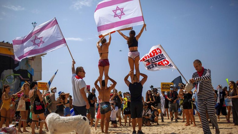 A man holds a sign showing Prime Minister Benjamin Netanyahu and his wife Sara during a protest against governments decision to close beaches during the three-week nationwide lockdown due to the coronavirus pandemic, in Tel Aviv, Israel, Saturday, Sept 19, 2020. Israel went back into a full lockdown on Friday to try to contain a coronavirus outbreak that has steadily worsened for months as its government has been plagued by indecision and infighting. Hebrew sighs reads