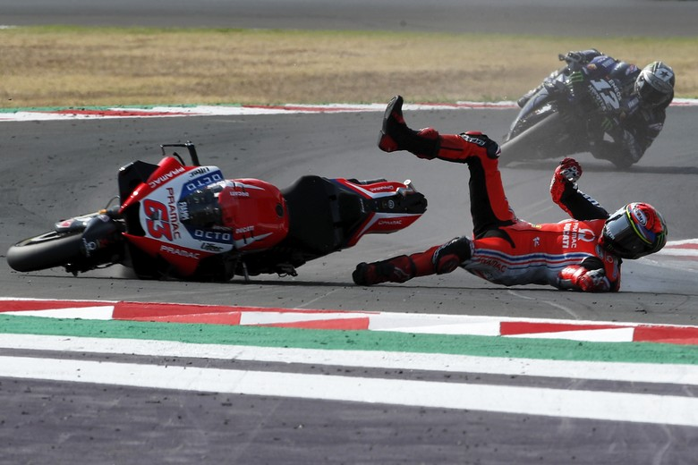MotoGP rider Francesco Bagnaia of Italy falls down when leading the race ahead of Maverick Vinales of Spain, in the background, during the Emilia Romagna Motorcycle Grand Prix at the Misano circuit in Misano Adriatico, Italy, Sunday, Sept. 20, 2020. (AP Photo/Antonio Calanni)