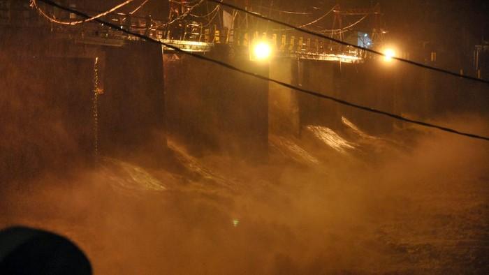Pengendara motor melintas di atas jembatan sungai Warga memotret derasnya debit air sungai Ciliwung di Bendung Katulampa, Kota Bogor, Jawa Barat, Senin (21/9/2020).  Tingginya intensitas curah hujan di wilayah Puncak, Kabupaten Bogor menyebabkan ketinggian muka air di Bendung Katulampa mengalami peningkatan hingga mencapai 250 cm atau status Siaga 1 sehingga warga di bantaran Sungai Ciliwung diminta untuk waspada. ANTARA FOTO/Arif Firmansyah/pras.