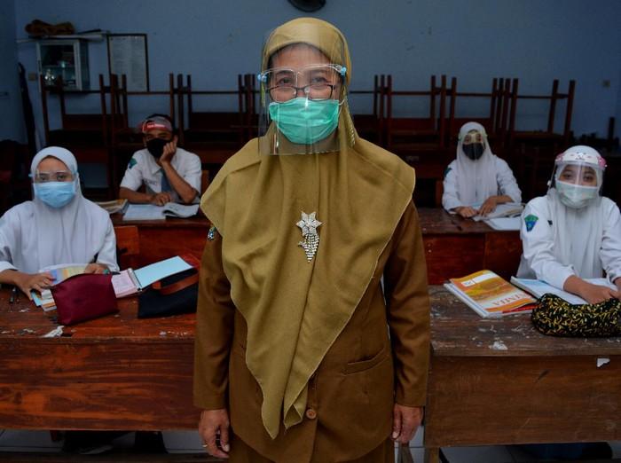 Seorang guru sekolah dasar mengajar pelajaran agama di rumah muridnya di Kelurahan Pesantren, Kota Kediri, Jawa Timur, Selasa (15/9/2020). Pembelajaran kelompok kecil di rumah siswa sekali dalam sebulan tersebut sebagai evaluasi penguasan materi pelajaran sekaligus upaya penyegaran agar siswa tidak bosan mengikuti pembelajaran jarak jauh.
