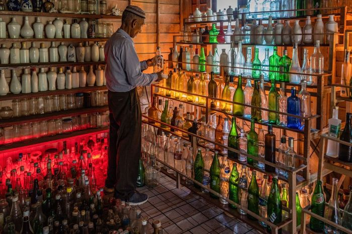 TOPSHOT - This picture taken on September 12, 2020 shows Tengku Mohamad Ali Mansor inspecting a glass bottle at his bottle museum in Penarik village in the Setiu district of the eastern Malaysian state of Terengganu. - An elderly Malaysians quest to rid the countrys beaches of washed-up glass led to him amassing a collection of thousands of bottles, now displayed in a colourful seaside museum. (Photo by Mohd RASFAN / AFP)