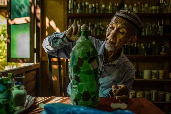 Di saat masa pandemi seperti ini, dia pun menyibukkan diri dengan merekatkan pecahan kaca untuk mebmuat botol lebih terlihat estetik. (AFP)