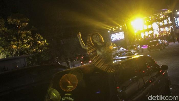 Kemeriahan penonton konser drive in perdana di Yogyakarta yang diselenggarakan di Sleman City Hall, Yogyakarta, Minggu (20/09/2020). Penyelenggaraan hari kedua konser drive in yang pertama kali di Yogyakarta ini dimeriahkan oleh pertunjukan band Jikustik yang membawakan sejumlah lagu hits mereka. detikcom/Pius Erlangga
