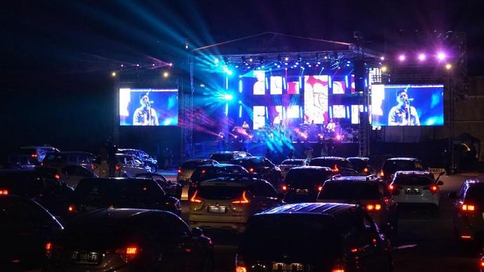 Penonton menyaksikan penampilan band Jikustik dari dalam mobil saat konser musik drive-in di Sleman City Hall, D.I Yogyakarta, Minggu (20/9/2020). Konser musik drive-in pertama di Yogyakarta itu digelar dengan menerapkan protokol kesehatan untuk mencegah penyebaran COVID-19. ANTARA FOTO/Andreas Fitri Atmoko/aww.