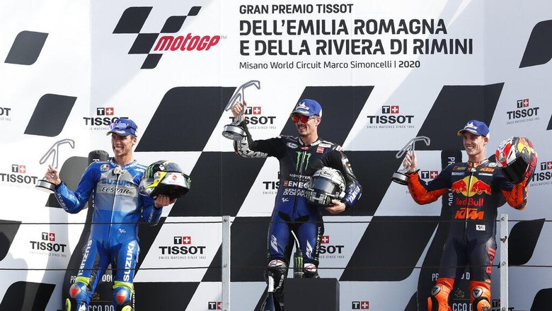 Second placed Joan Mir, winner Maverick Vinales and third placed Pol Espargaro, al three of Spain, pose on the podium of the MotoGP race of the Emilia Romagna Motorcycle Grand Prix at the Misano circuit in Misano Adriatico, Italy, Sunday, Sept. 20, 2020. (AP Photo/Antonio Calanni)