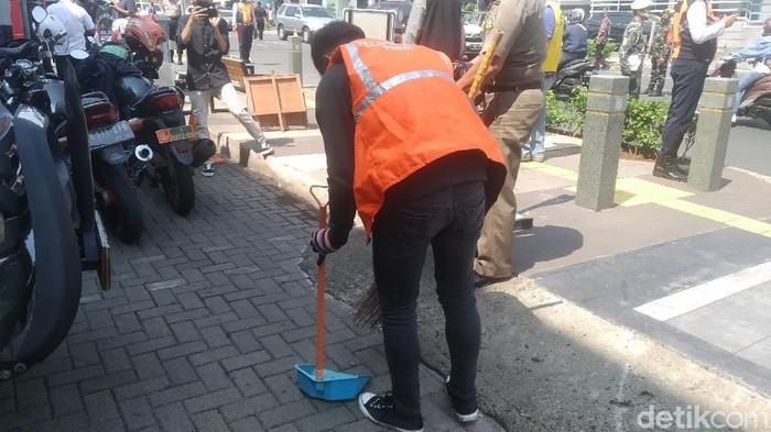 Pelanggar protokol kesehatan dihukum nyapu jalanan (Wilda Hayatun Nufus/detikcom).