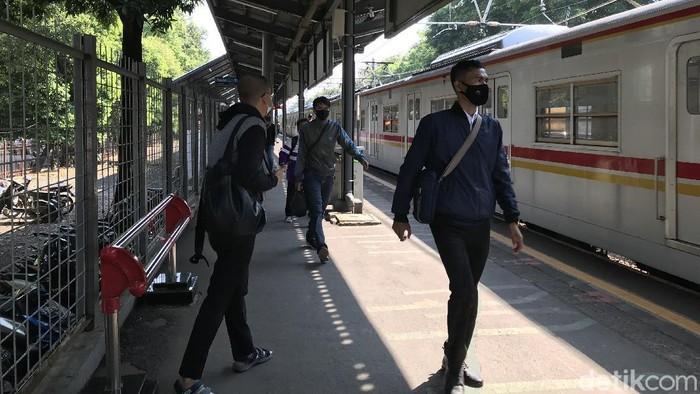 Penumpang KRL yang masih menggunakan masker scuba-buff di Stasiun Kalibata