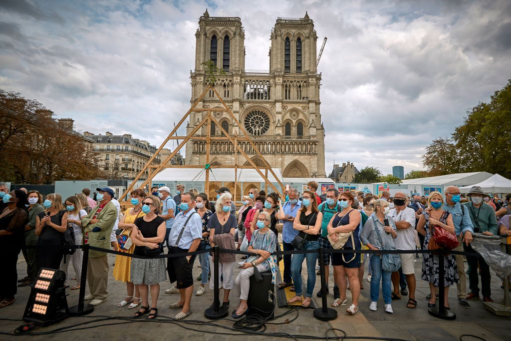 PARIS, FRANCE - SEPTEMBER 19: A member of the Charpentiers sans Frontièrs (Carpenters without Borders) works on the reconstruction of one of the missing timber frames of Notre-Dame Cathedral that was destroyed by the fire in front of the Cathedral on September 19, 2020 in Paris, France. Part of the 37th edition of the European Heritage Days, the iconic Parisian landmark aims at informing the public of the reconstruction plans related to the April 15, 2019 fire and aims to imporve the public's knowledge of Notre-Dame's architecture and history. The extensive damage to the roof and spire of the 13th-century Notre Dame de Paris cathedral have proven reconstruction process to be much more complex than many anticipated. (Photo by Kiran Ridley/Getty Images)