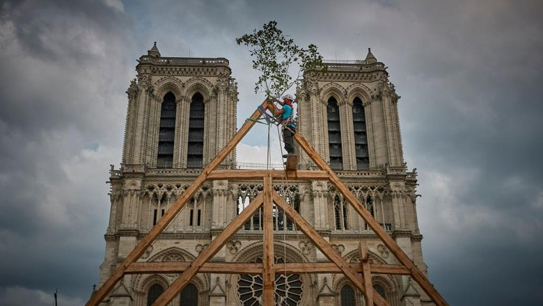 PARIS, FRANCE - SEPTEMBER 19: A member of the Charpentiers sans Frontièrs (Carpenters without Borders) works on the reconstruction of one of the missing timber frames of Notre-Dame Cathedral that was destroyed by the fire in front of the Cathedral on September 19, 2020 in Paris, France. Part of the 37th edition of the European Heritage Days, the iconic Parisian landmark aims at informing the public of the reconstruction plans related to the April 15, 2019 fire and aims to imporve the publics knowledge of Notre-Dames architecture and history. The extensive damage to the roof and spire of the 13th-century Notre Dame de Paris cathedral have proven reconstruction process to be much more complex than many anticipated. (Photo by Kiran Ridley/Getty Images)