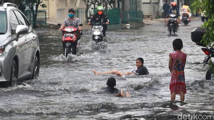Pasca hujan deras semalem, terdapat genangan air di depan Perumahan Green Garden, Kedoya, Jakarta. Genangan ini menjadi tempat main anak-anak.