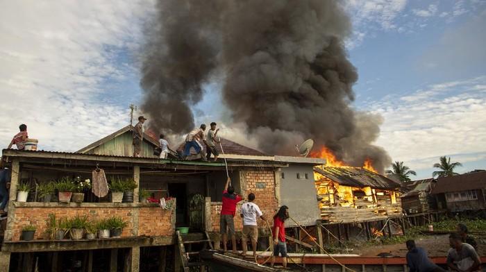 Warga menyelamatkan barang-barang miliknya saat terjadi kebakaran di lorong Pahlawan 35 ilir, Tanggo Buntung, Palembang, Sumatera Selatan, Selasa (22/9/2020). Penyebab kebakaran yang terjadi di pemukiman padat penduduk tersebut, saat ini masih dalam penyelidikan pihak kepolisian. ANTARA FOTO/Nova Wahyudi/foc.