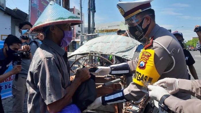 Di HUT Lalu Lintas ke-65, polisi Ngawi membagikan masker dan sembako. Para tukang becak yang terdampak pandemi COVID-19 mengaku senang.