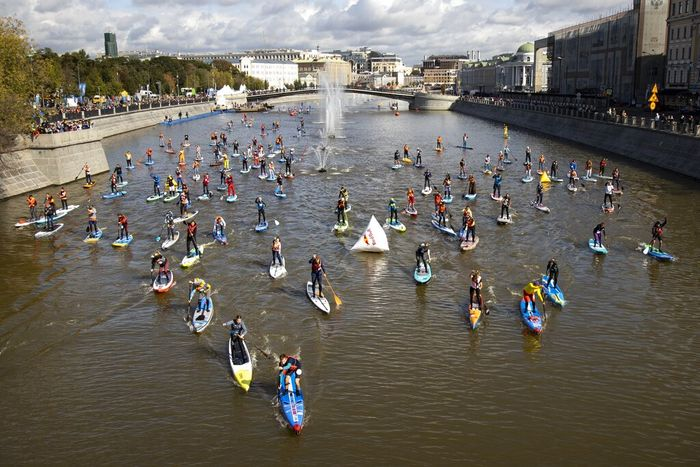 People steer their SUP boards along the Moscow River Channel during a SUP (Stand Up Paddle)-Surfing festival in Moscow, Russia, Saturday, Sept. 19, 2020. (AP Photo/Alexander Zemlianichenko)