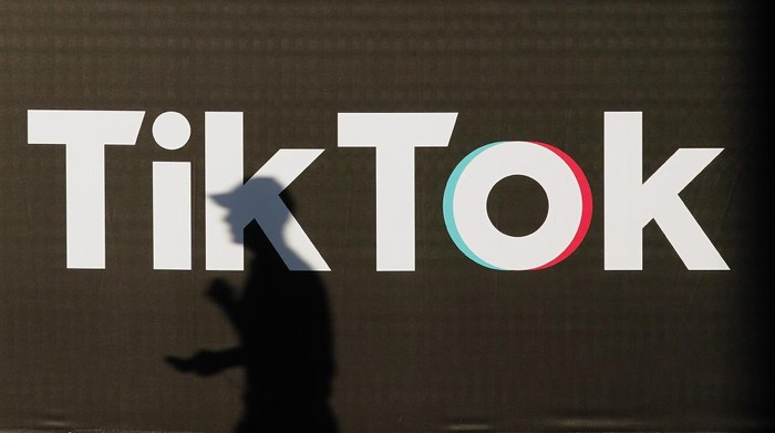 BERLIN, GERMANY - SEPTEMBER 21: A young man holding a smartphone casts a shadow as he walks past an advertisement for social media company TikTok on September 21, 2020 in Berlin, Germany. U.S. President Donald Trump has given preliminary approval for Oracle, Walmart and other investors to take over TikTok and create a new U.S.-based company called TikTok Global. (Photo by Sean Gallup/Getty Images)