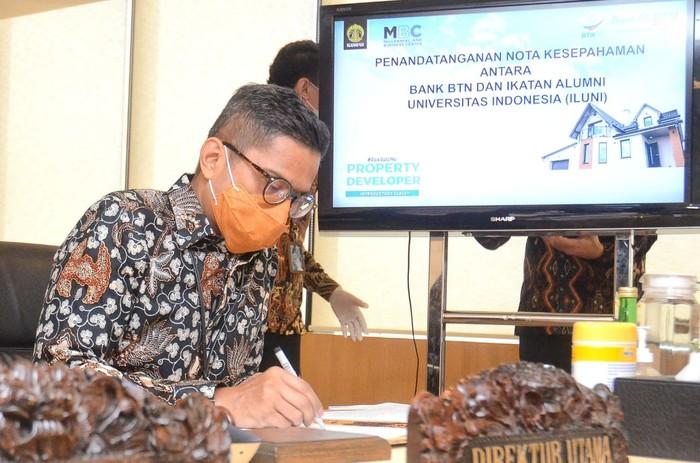 Direktur Utama PT Bank Tabungan Negara (Persero) Tbk. Pahala Nugraha Mansury didampingi Direktur Nixon LP Napitupulu bersama Ketua Umum Ikatan Alumni Universitas Indonesia (ILUNI UI) memamerkan naskah Nota Kesepahaman usai penandatangan Memorandum of Understanding (MoU) secara virtual di Jakarta, Rabu (23/9). Melalui MoU tersebut, kedua institusi bekerja sama menggelar kegiatan Ruang Temu Property Developer, sebuah program pelatihan level dasar untuk alumni UI yang berniat terjun sebagai pelaku usaha pengembang properti. Kerja sama antara Bank BTN dengan ILUNI UI juga terbuka untuk program riset di bidang perumahan, konsultasi di bidang perumahan, serta kerja sama lainnya yang menguntungkan dan disepakati kedua belah pihak.