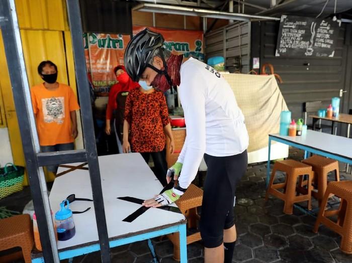 Gubernur Jawa Tengah, Ganjar Pranowo, memasang lakban jaga jarak di sejumlah bangku warung makan di kawasan Semarang. Hal itu dilakukan untuk cegah Corona.