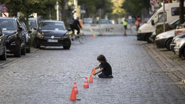 Tak hanya menggambar, seorang anak juga tampak asyik bermain menyusun traffic cone mini di tengah jalan yang ditutup untuk memperingati Hari Bebas Kendaraan Internasional.