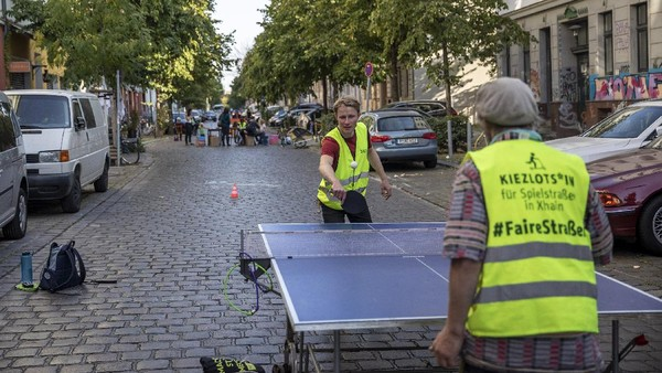 Tampak pula dua orang warga asyik bermain tenis meja di jalan yang ditutup untuk memperingati Hari Bebas Kendaraan Internasional.