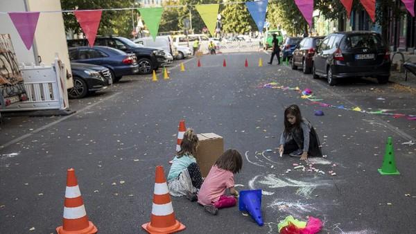 Sejumlah anak tampak asyik menggambar di tengah jalan yang berada di kawasan distrik Kreuzberg, Berlin, Jerman, Selasa (22/9/2020) waktu setempat.