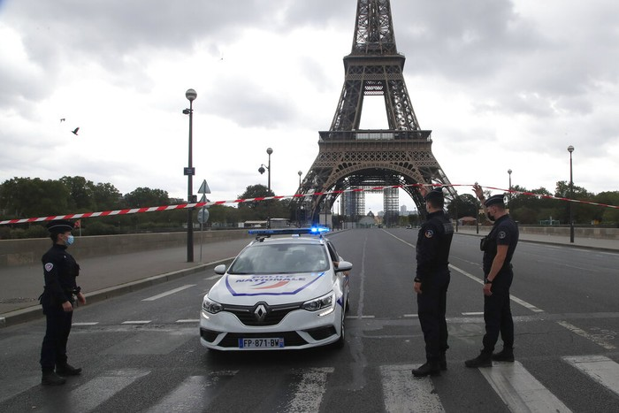 French police officers secure the bridge leading to the Eiffel Tower, Wednesday, Sept. 23, 2020 in Paris. Paris police have blockaded the area around the Eiffel Tower after a phone-in bomb threat. (AP Photo/Michel Euler)