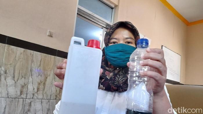 Petugas menunjukkan hasil air sumur warga yang sempat bikin heboh karena mengeluarkan BBM yang kini mulai jernih